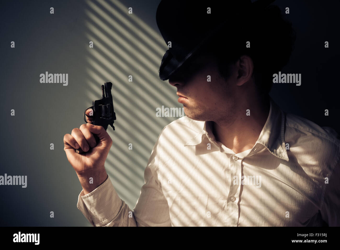 Young man with gun by the window is covered in shadows from the blinds - Stock Image