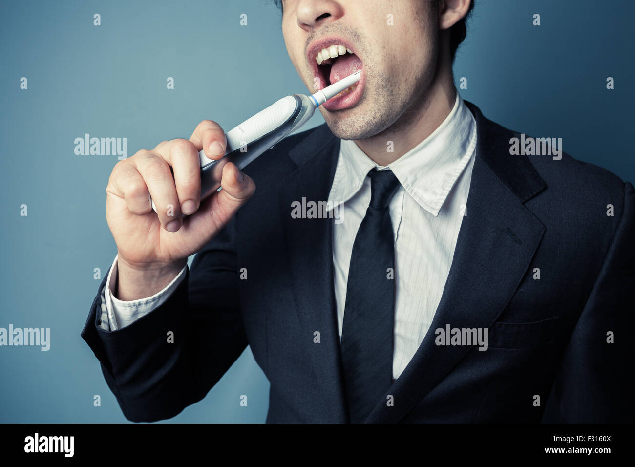 Young businessman is brushing his teeth with an electric toothbrush - Stock Image