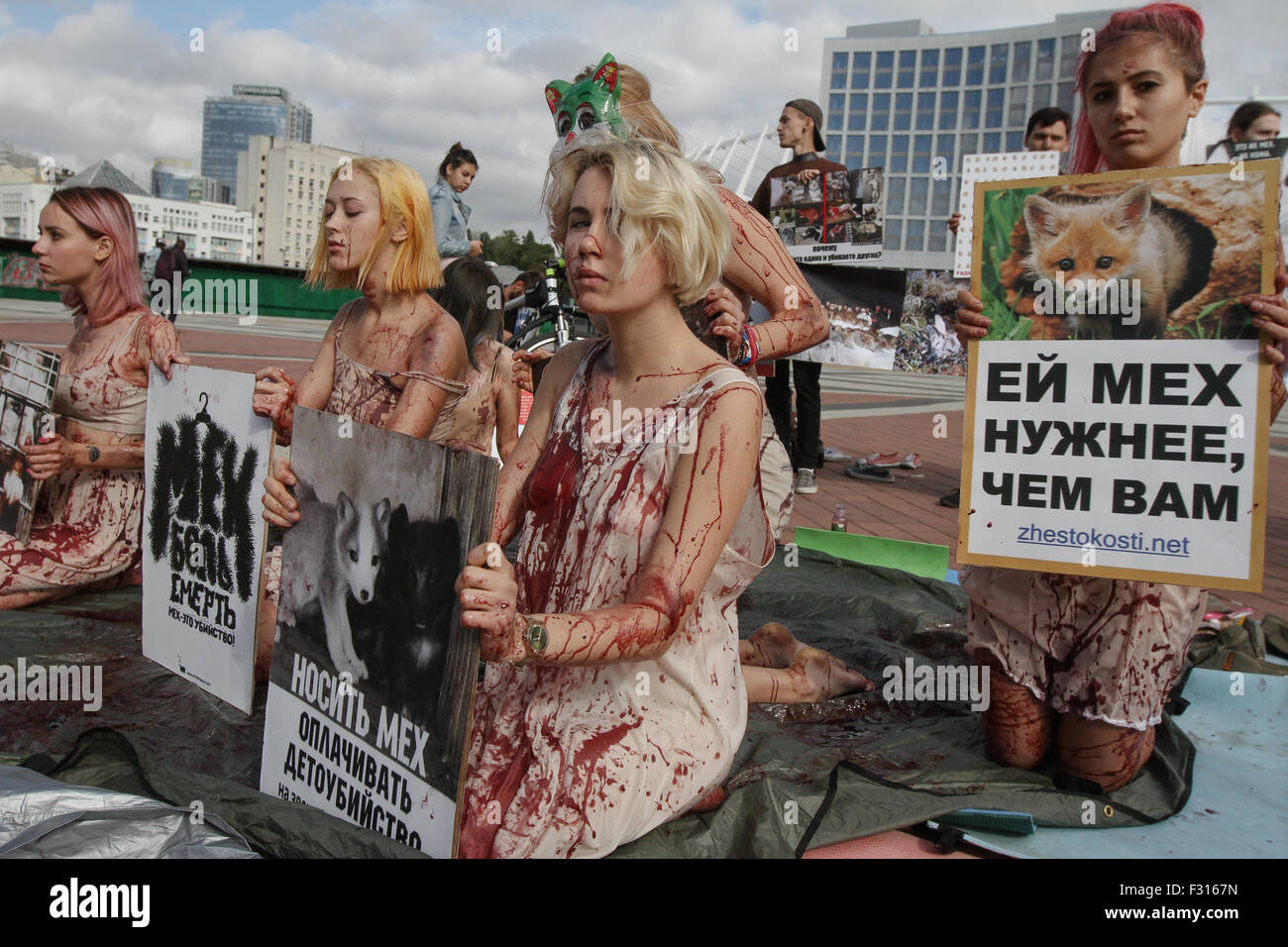 "Kiev, Ukraine. 27th Sep, 2015. Animal rights activists in bloodstained clothes hold a placard which says ""Fur is Stock Photo"