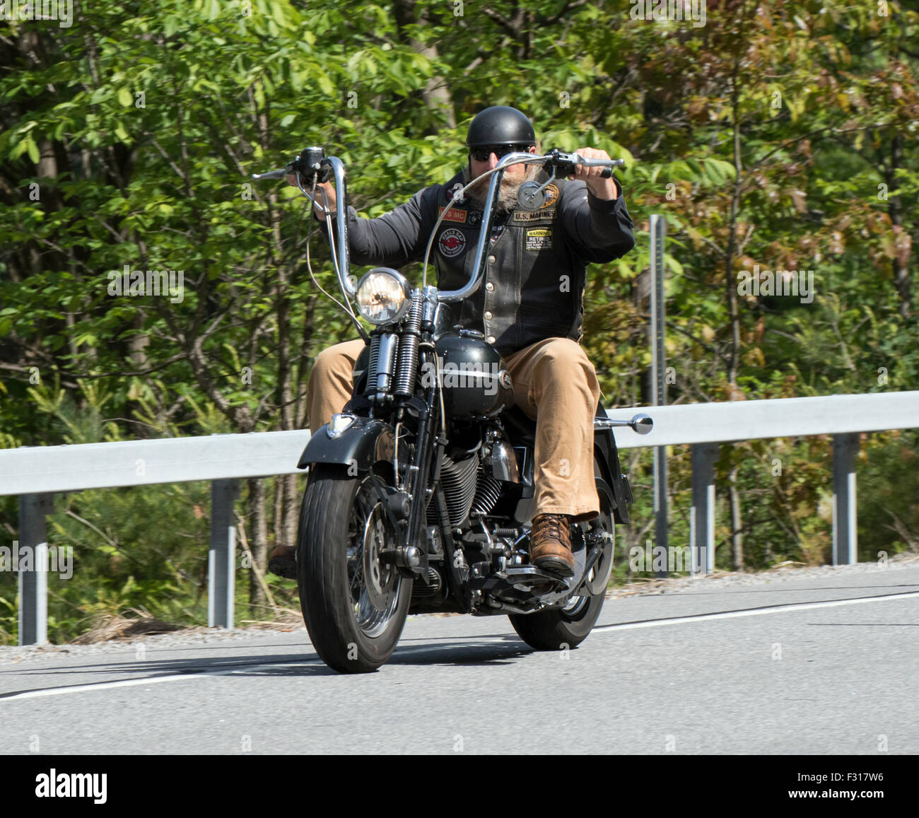 Man riding an old antique vintage Harley Davidson with ape