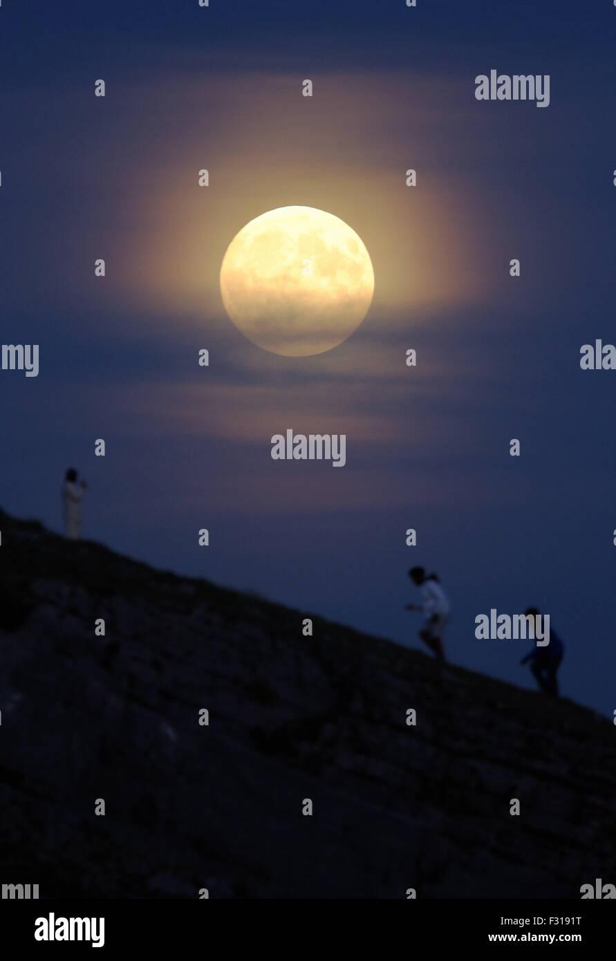 Mumbles UK. Sunday 27 September 2015   A full moon rises over Bracelet Bay, Mumbles in Swansea Bay, Wales UK. The - Stock Image