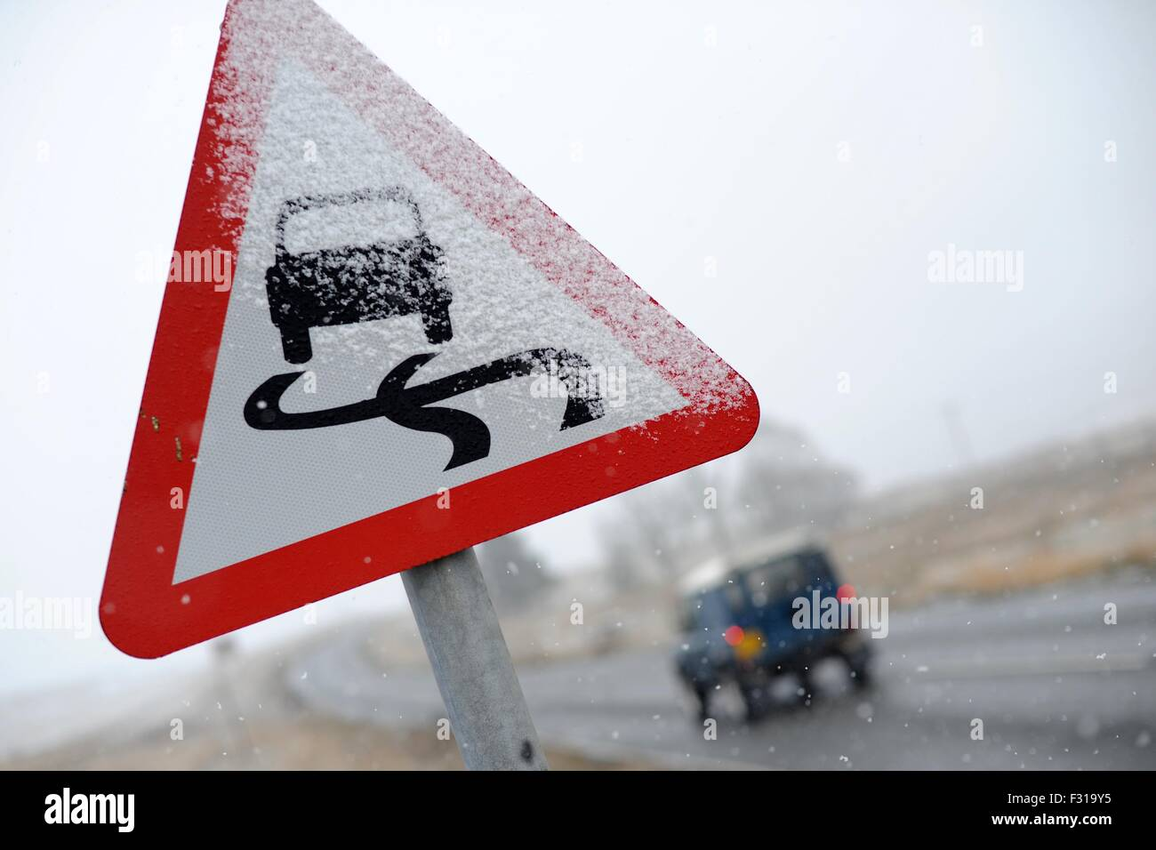 A road sign covered in snow warning car drivers of hazardous driving conditions. - Stock Image