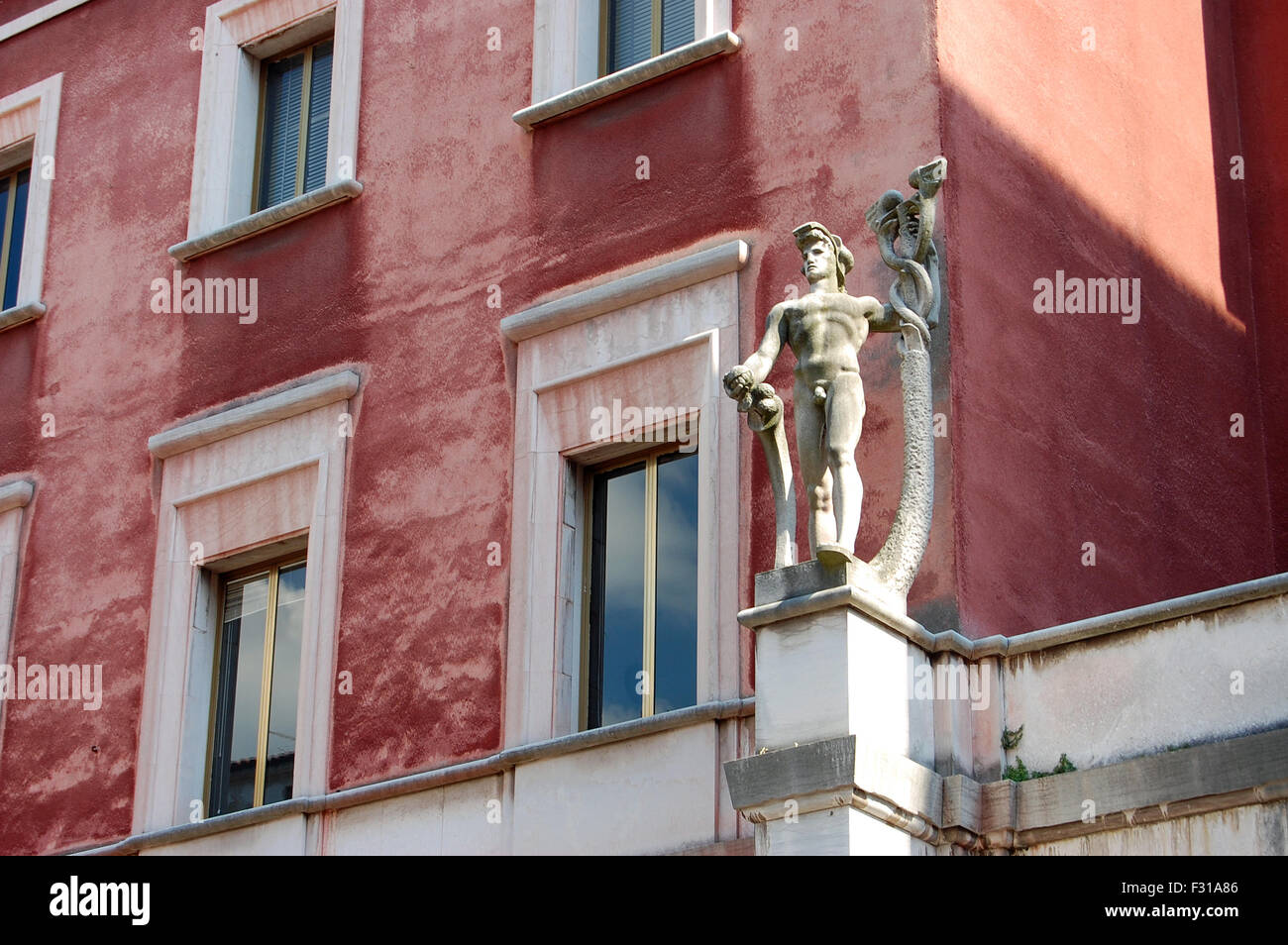 Statue set against the pink building of the Posta Italiane in Vicenza, Italy. - Stock Image
