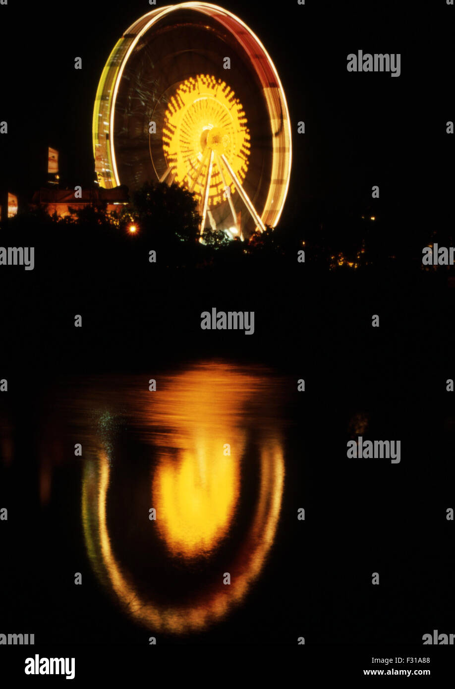Ferris wheel and its reflection at night in the water of the Donau (Blue Danube) during the Volksfest (festival) - Stock Image