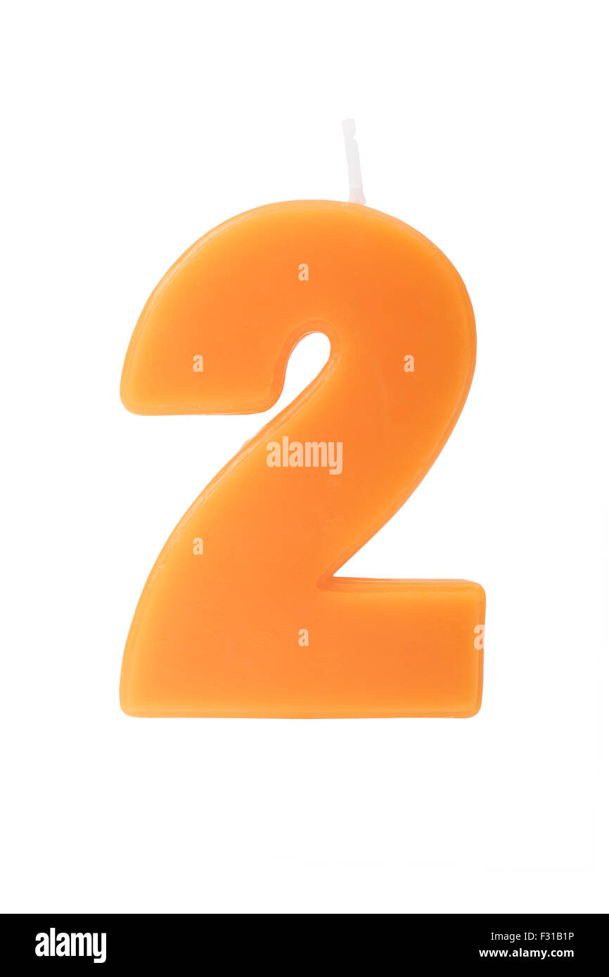 Orange birthday candle in the form of the number two on white background - Stock Image