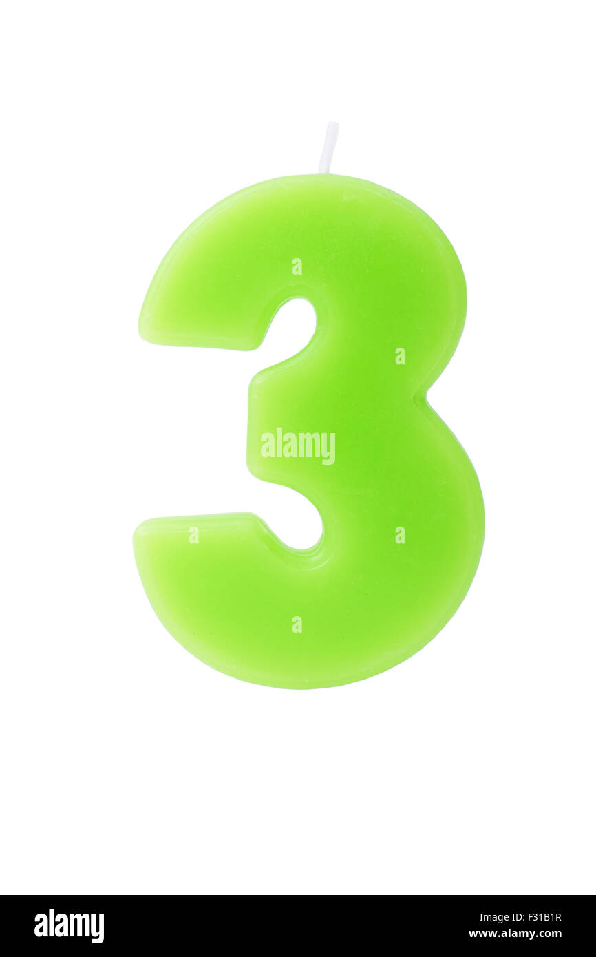 Green birthday candle in the form of the number three on white background - Stock Image