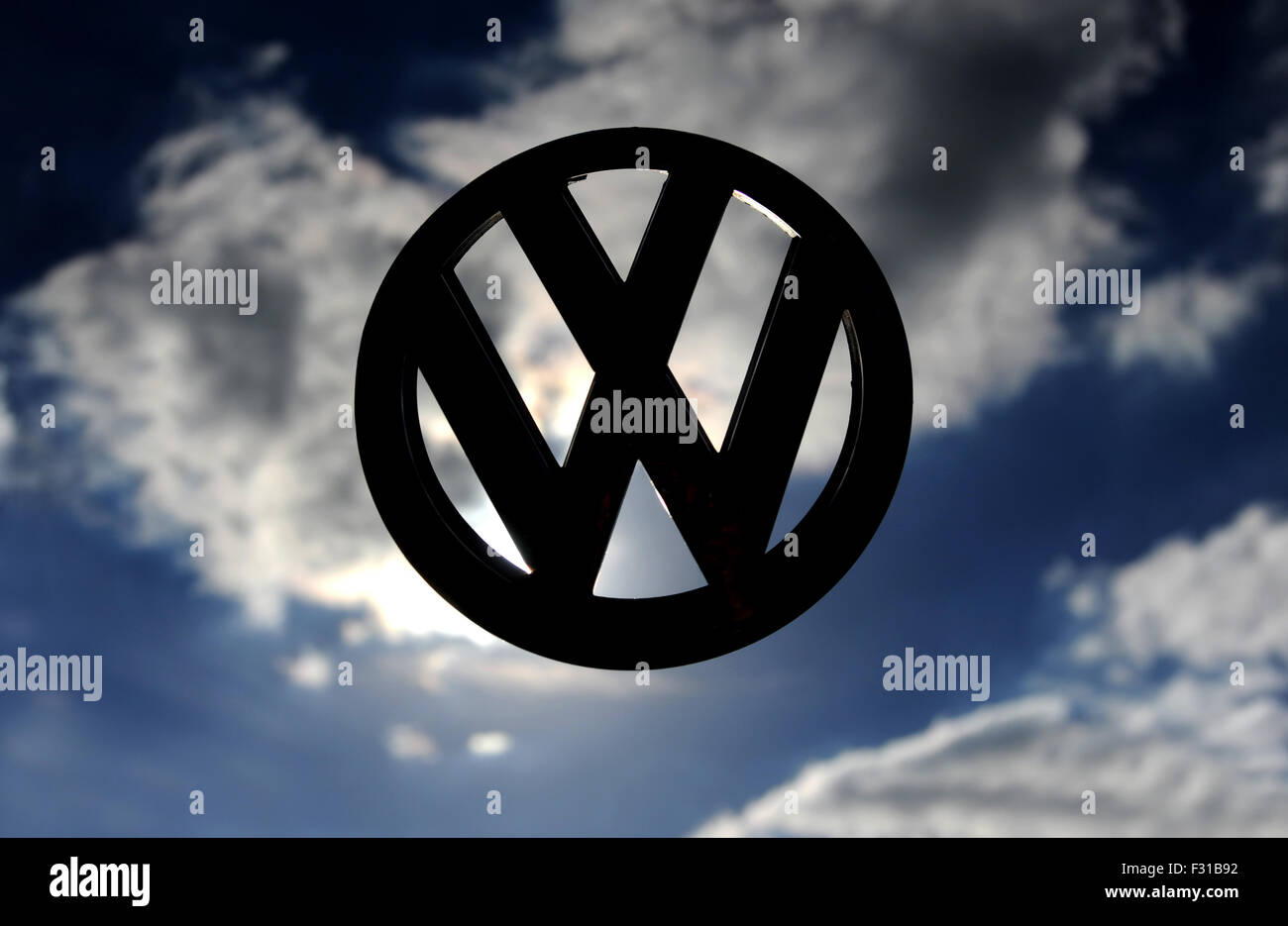 VW VOLKSWAGEN CAR BADGE AGAINST STORMY SKY RE EMISSIONS SCANDAL DIRTY ENGINES MOTOR INDUSTRY STORY LOGO EMBLEM TESTING - Stock Image