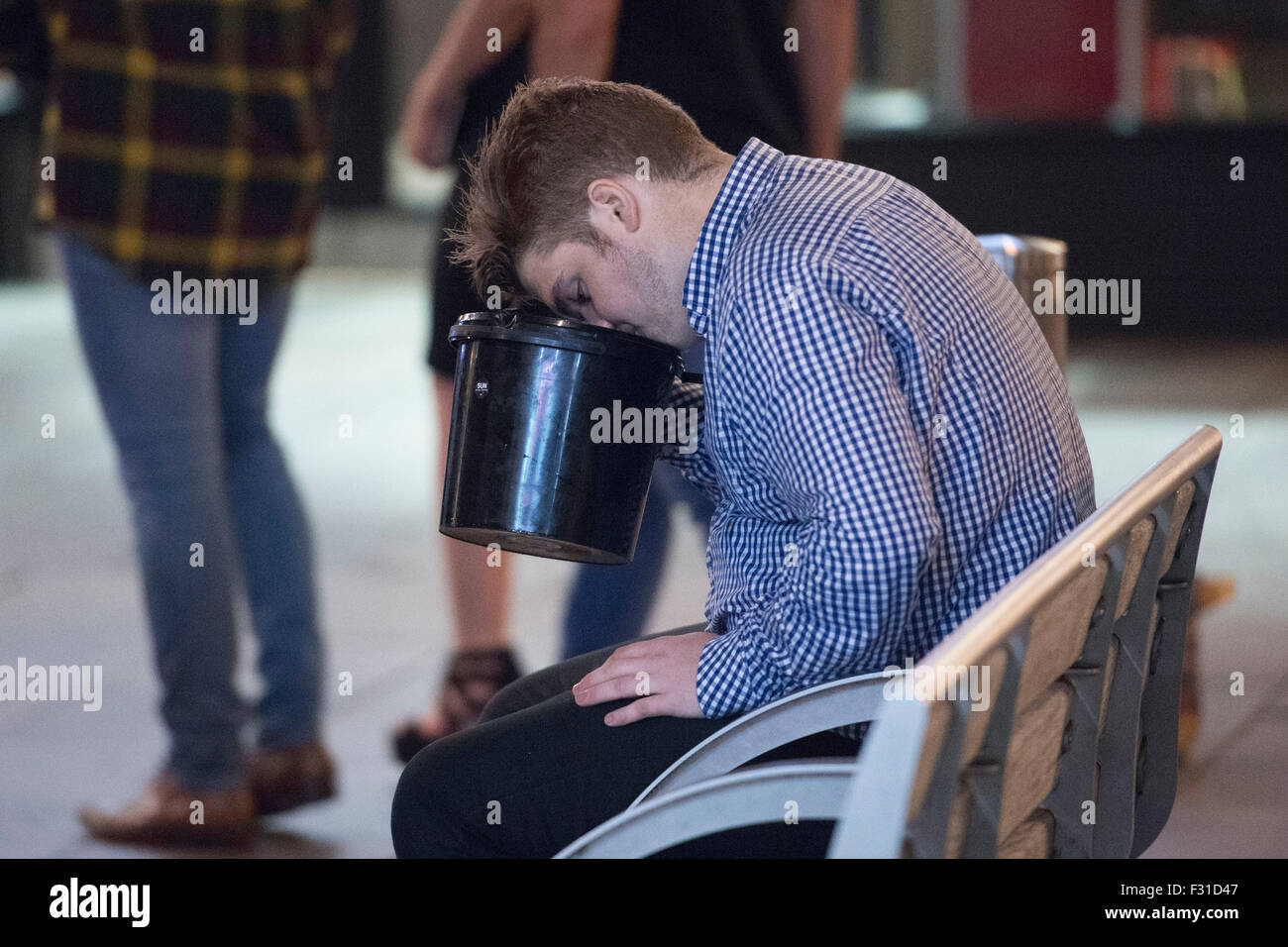 A man is sick into a bucket in Cardiff, South Wales. - Stock Image