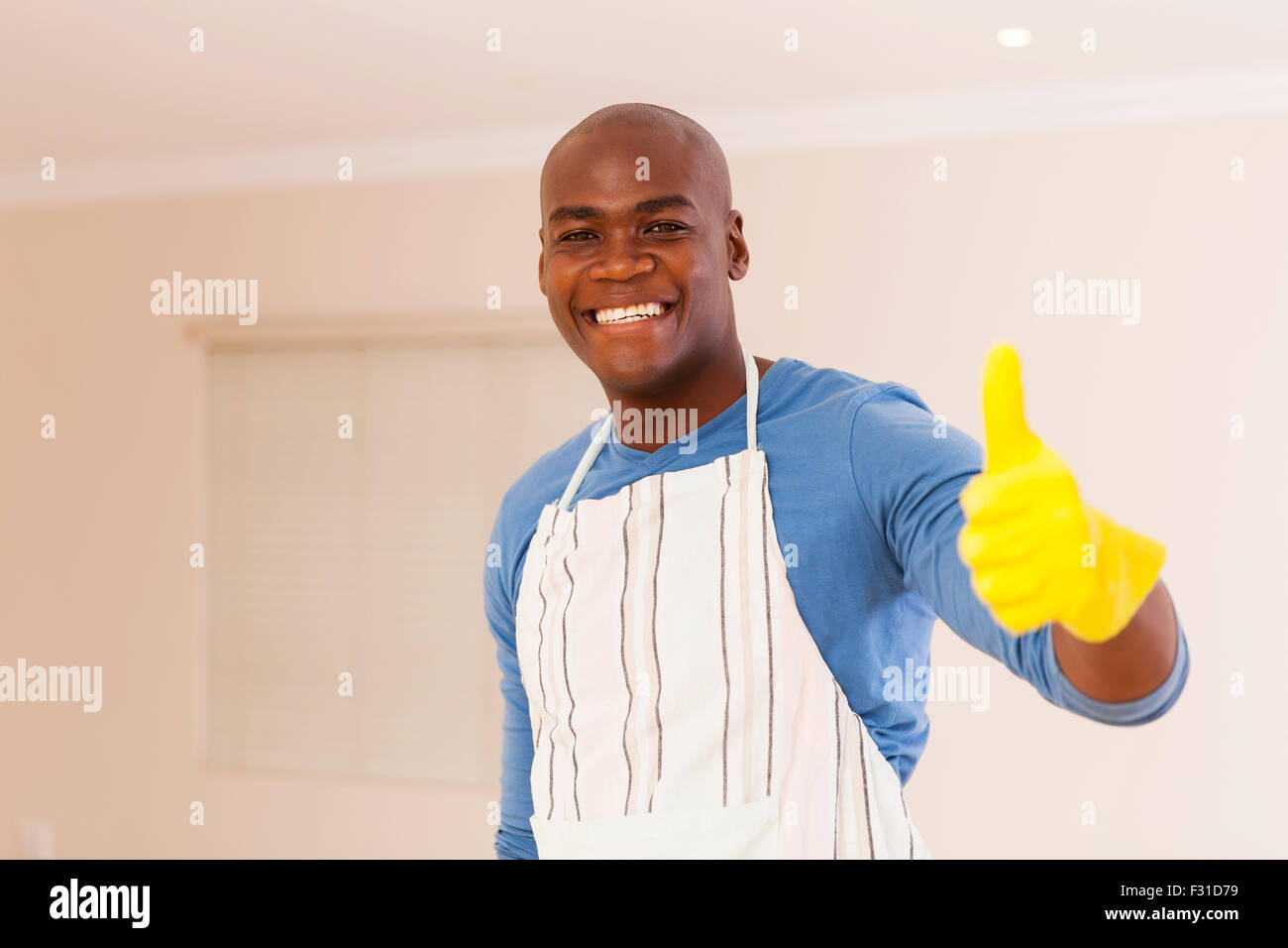 cheerful black man giving thumb up after doing housework - Stock Image