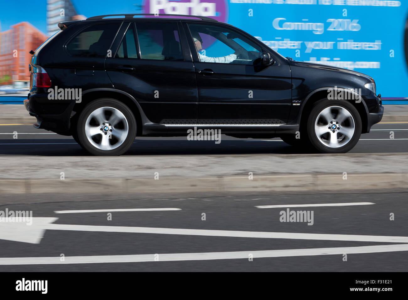 A blurred moving BMW X5 at speed motion blur on 'The Strand' at Liverpool One, Liverpool, Merseyside, UK - Stock Image
