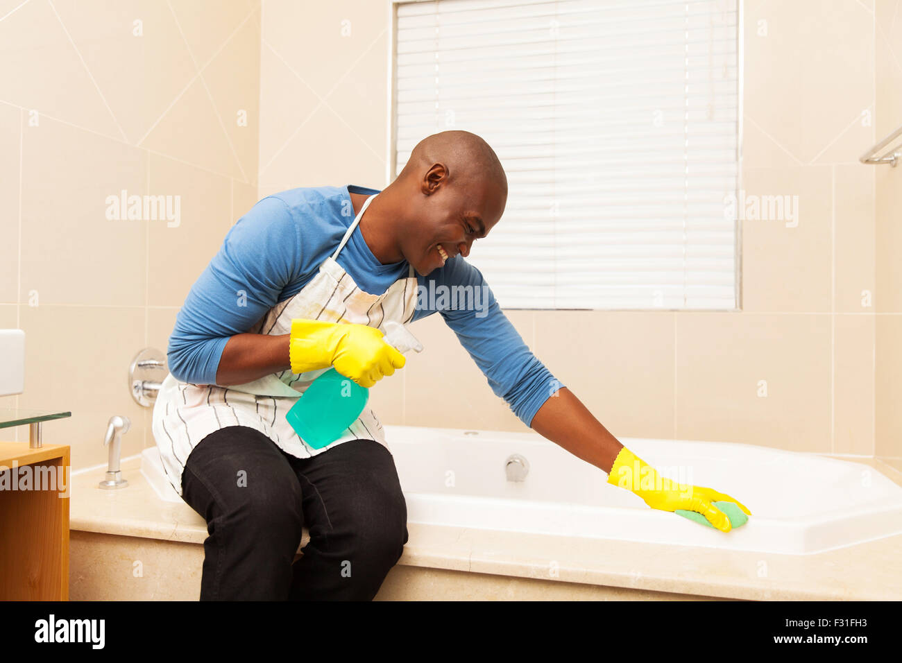 happy African American man cleaning up bathtub at home - Stock Image