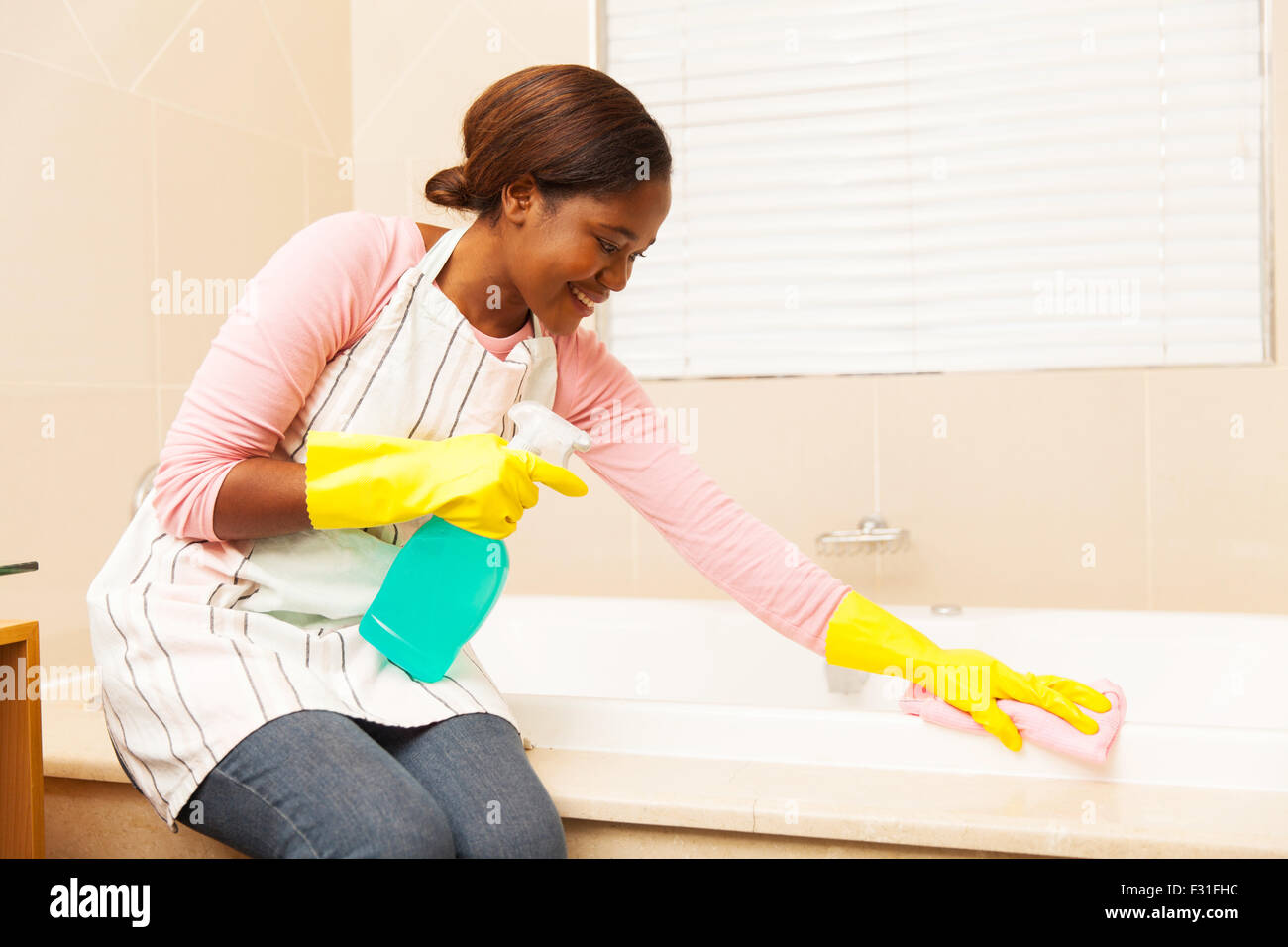 pretty African housewife cleaning up bathtub at home - Stock Image