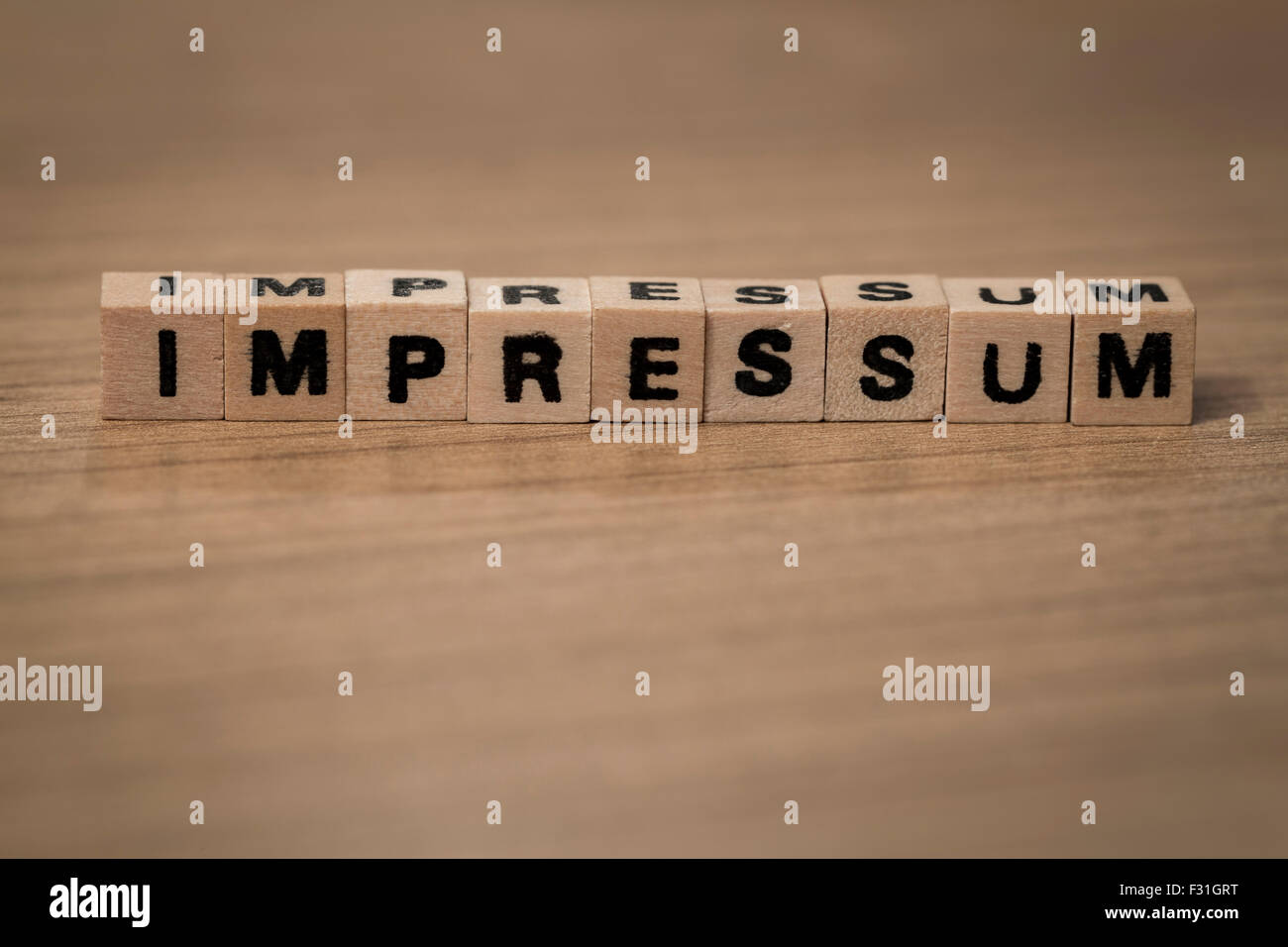 impressum (german imprint) written in wooden cubes on a desk - Stock Image