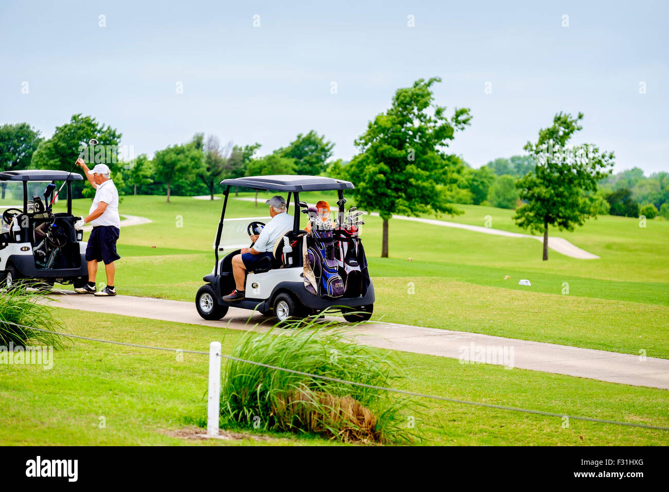 Men ride in golf carts on a cart path during a tournament at Hefner Golf course in Oklahoma City, Oklahoma, USA. - Stock Image