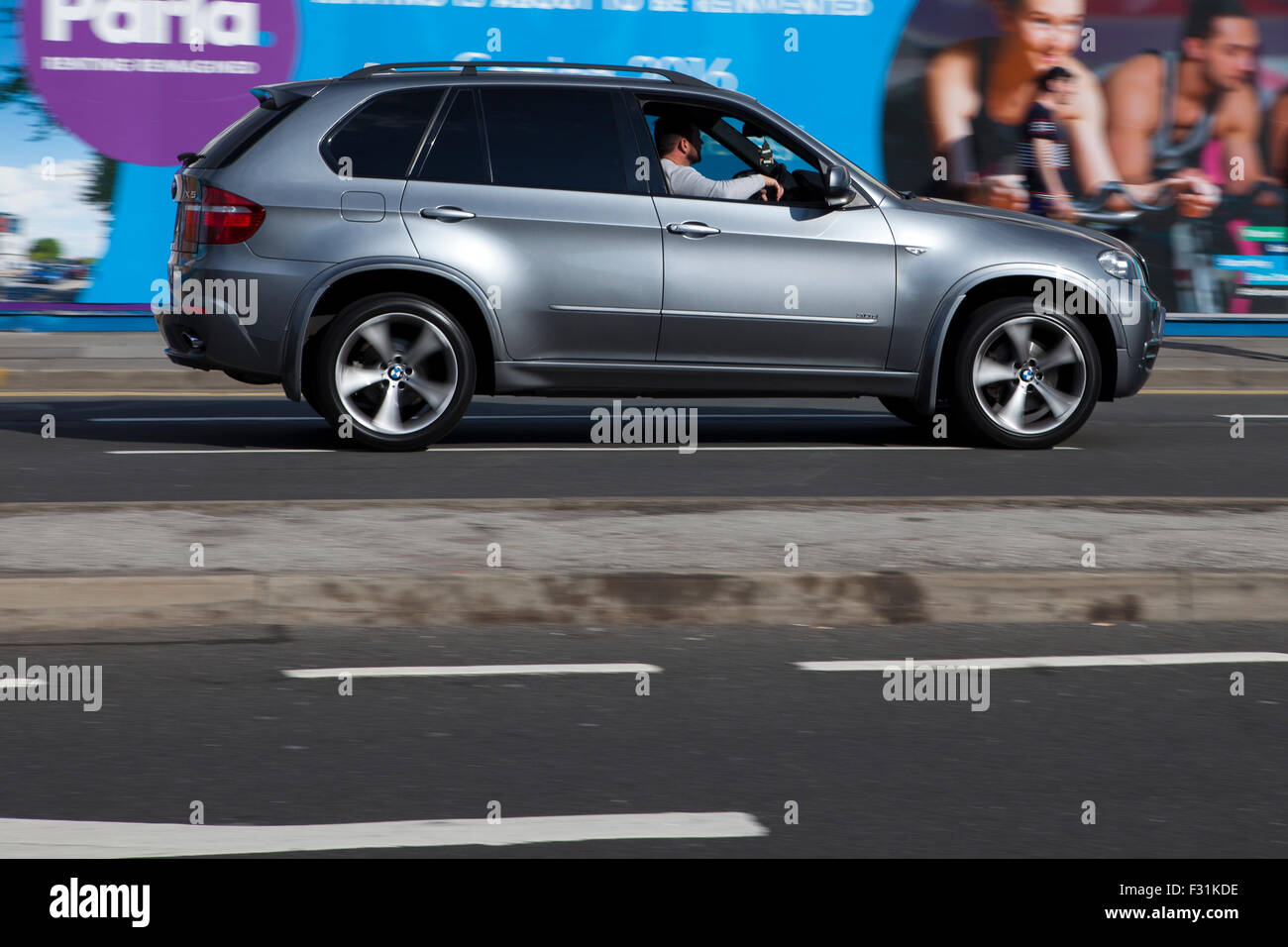 A blurred moving silver BMW X5 at speed motion blur on 'The Strand' at Liverpool One, Liverpool, Merseyside, - Stock Image
