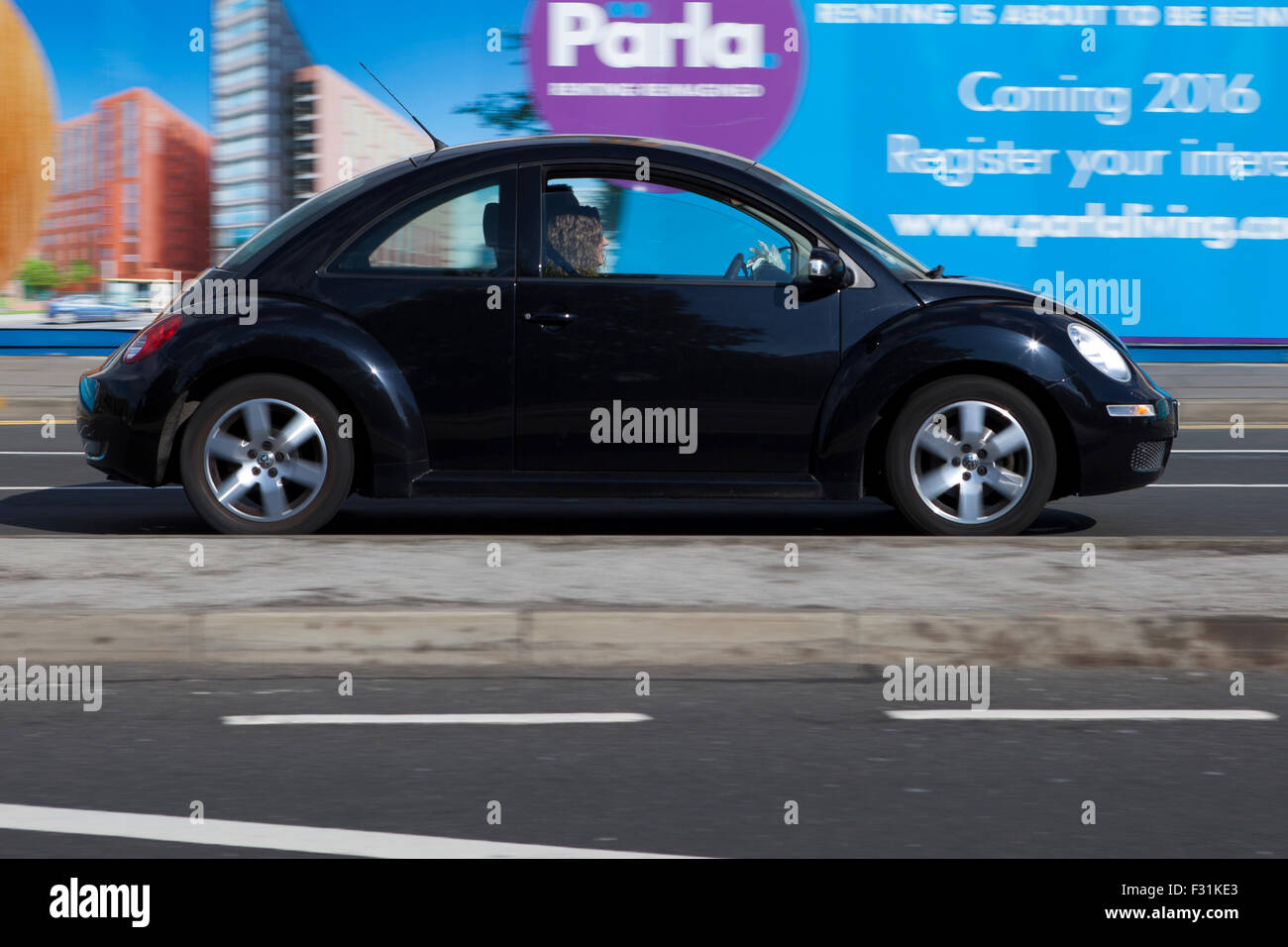 A blurred moving Volkswagen VW Beetle at speed motion blur on 'The Strand' at Liverpool One, Liverpool, - Stock Image