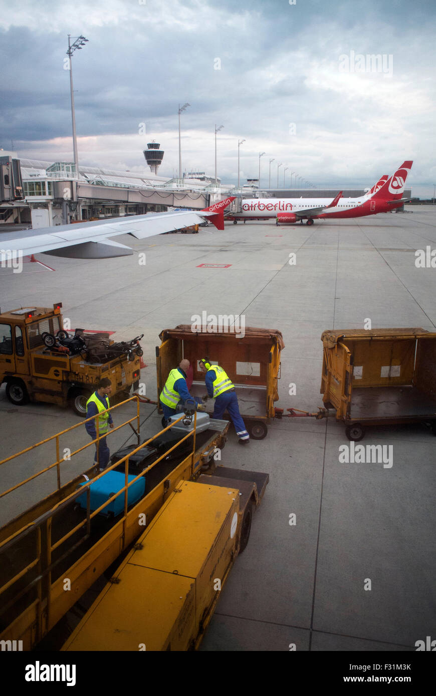 Baggage handers unloading baggage from an Air Berlin flight at Munich Airport, Germany. - Stock Image