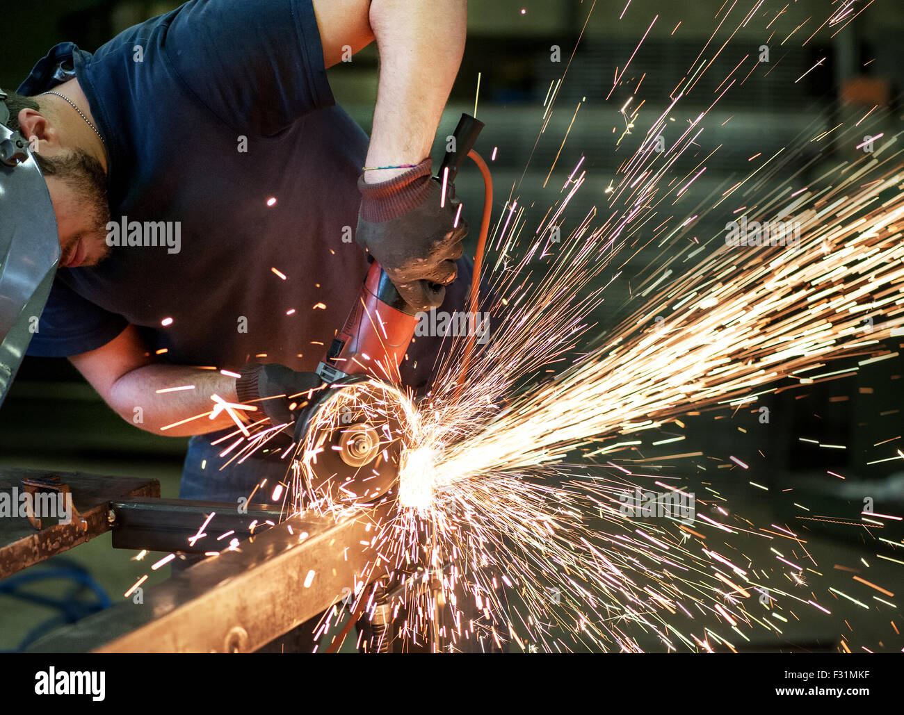 Metalworker cutting a steel bar using a hand held angle grinder power tool - Stock Image