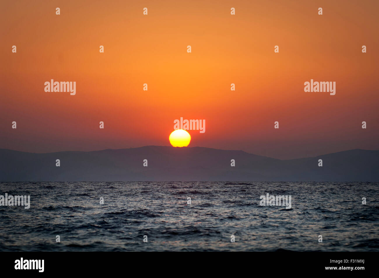Sun rise over western Turkey. Photographed from the Island of Lesbos, Greece. - Stock Image
