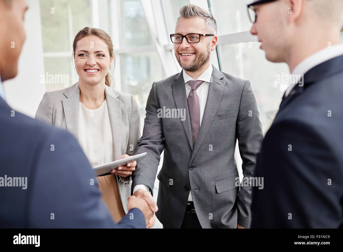 Happy colleagues looking at their business partner while greeting him - Stock Image