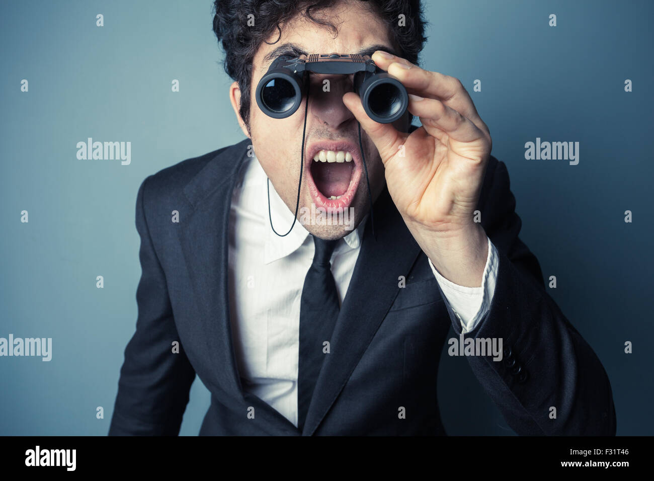 Young businessman is looking through binoculars and is surprised at what he sees - Stock Image