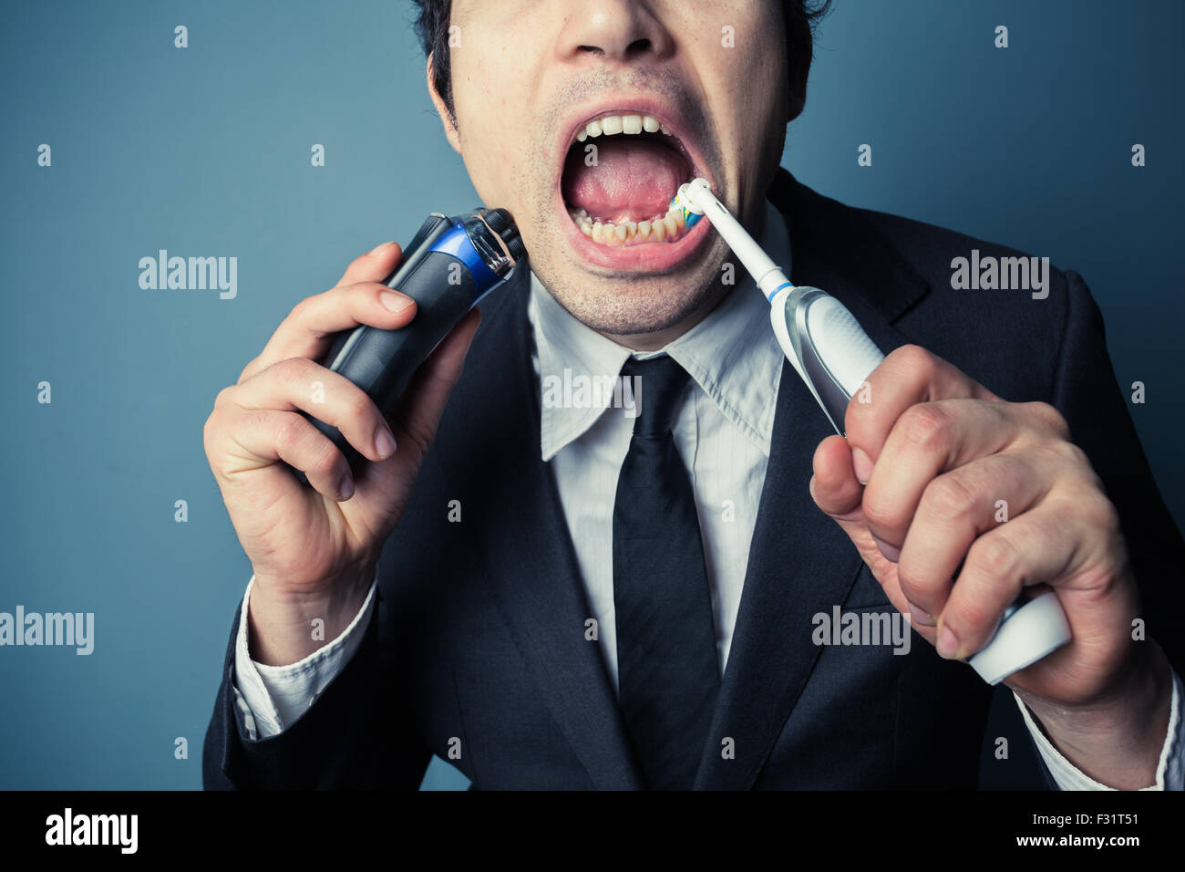 A stressed businessman is late and is shaving and brushing his teeth at the same time - Stock Image