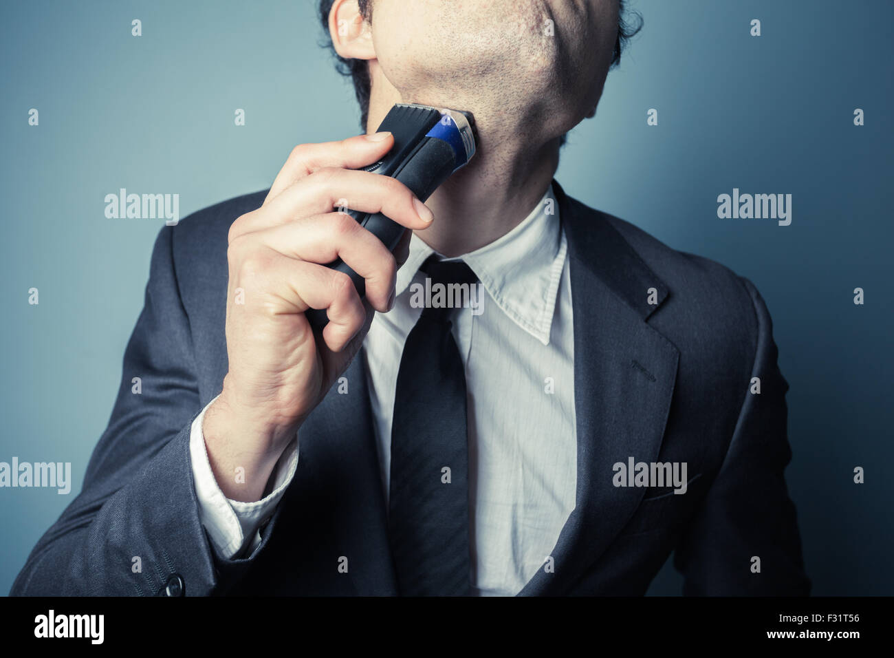 A young businessman is shaving with an electric razor - Stock Image