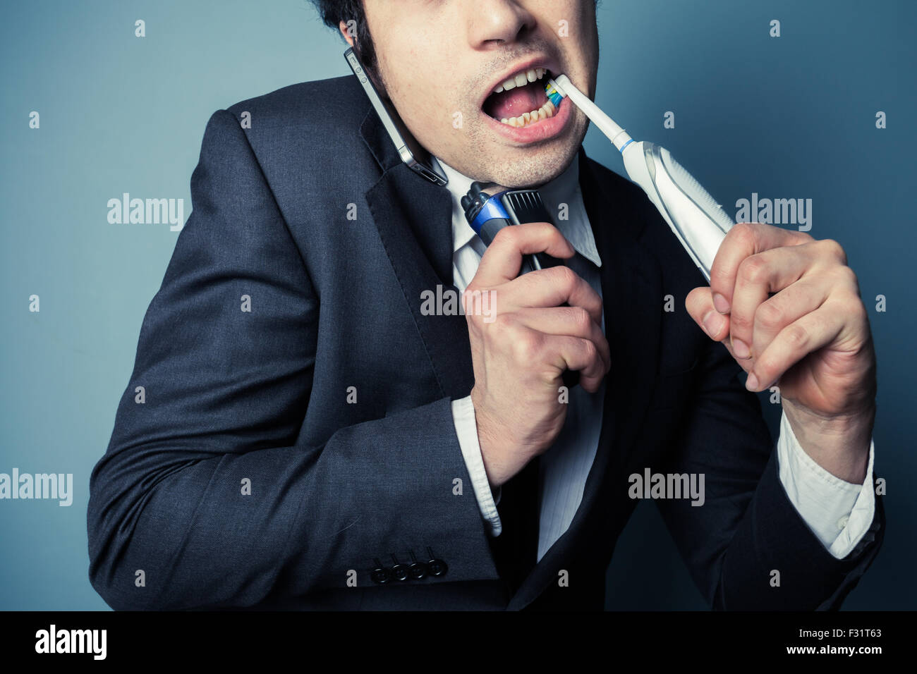 Stressed businessman is on the phone while brushing his teeth and shaving to save time - Stock Image