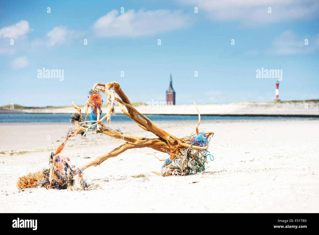 Driftwood with fishing nets logs on beach, Wangerooge, East Frisian Islands, Germany - Stock Image