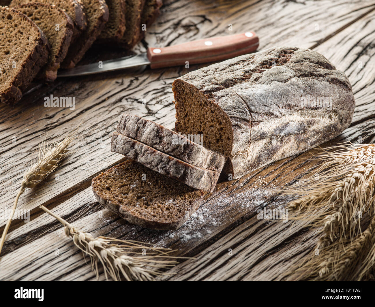 Sliced black bread on the old wooden plank. Stock Photo