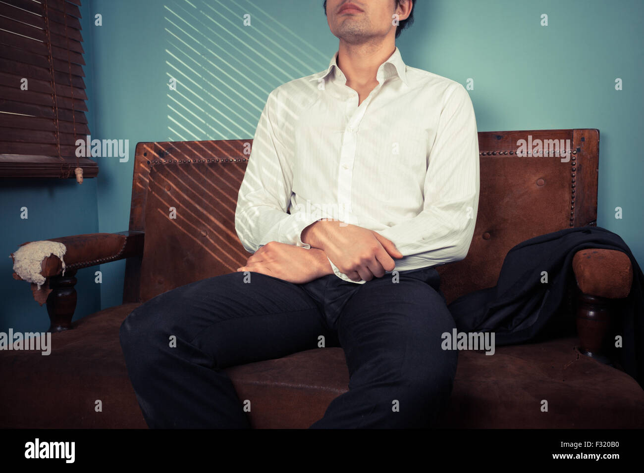 Young man is relaxing on an old sofa by the window on a sunny day - Stock Image