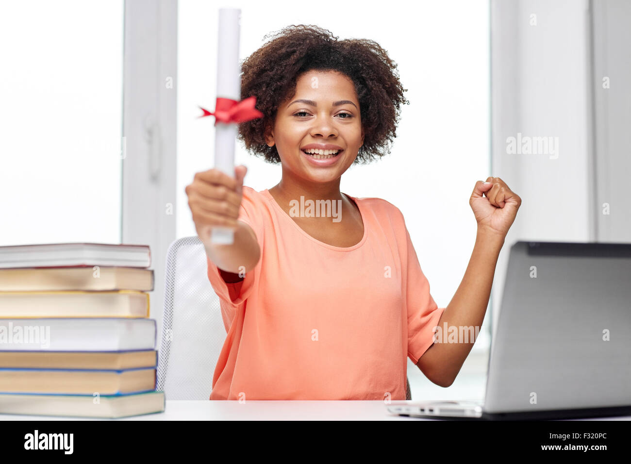 happy african woman with laptop, books and diploma - Stock Image