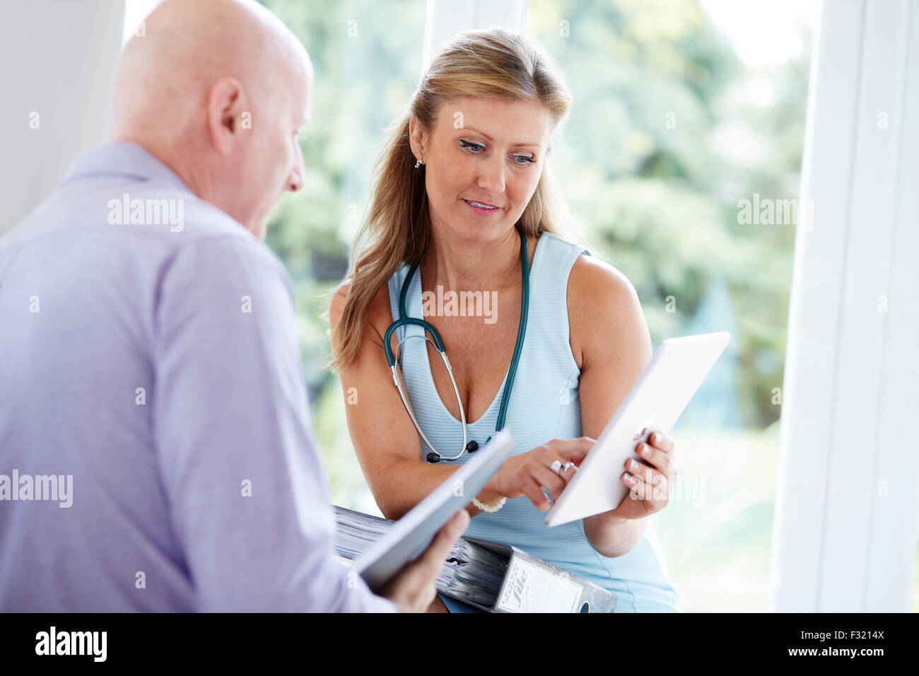 Doctor discussing notes with colleague - Stock Image