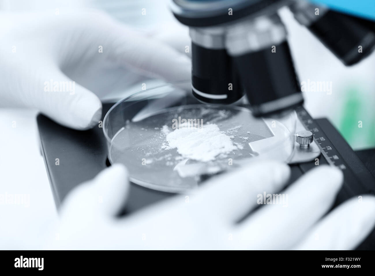 close up of hand with microscope and powder sample Stock Photo