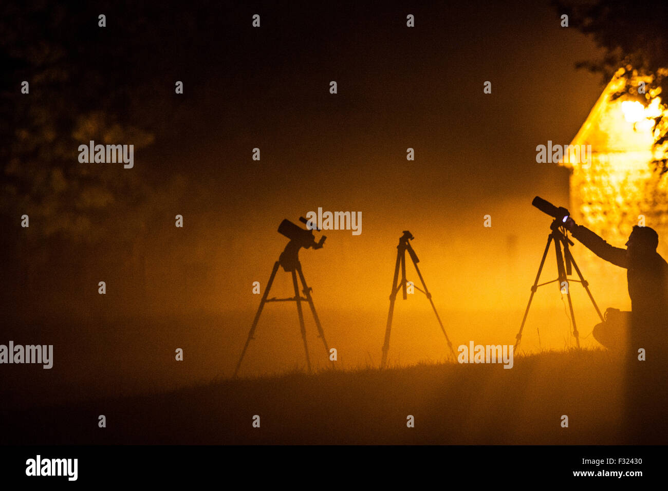 Silhouettes of photographers and tripods waiting to photograph the Blood Moon over Avebury. - Stock Image