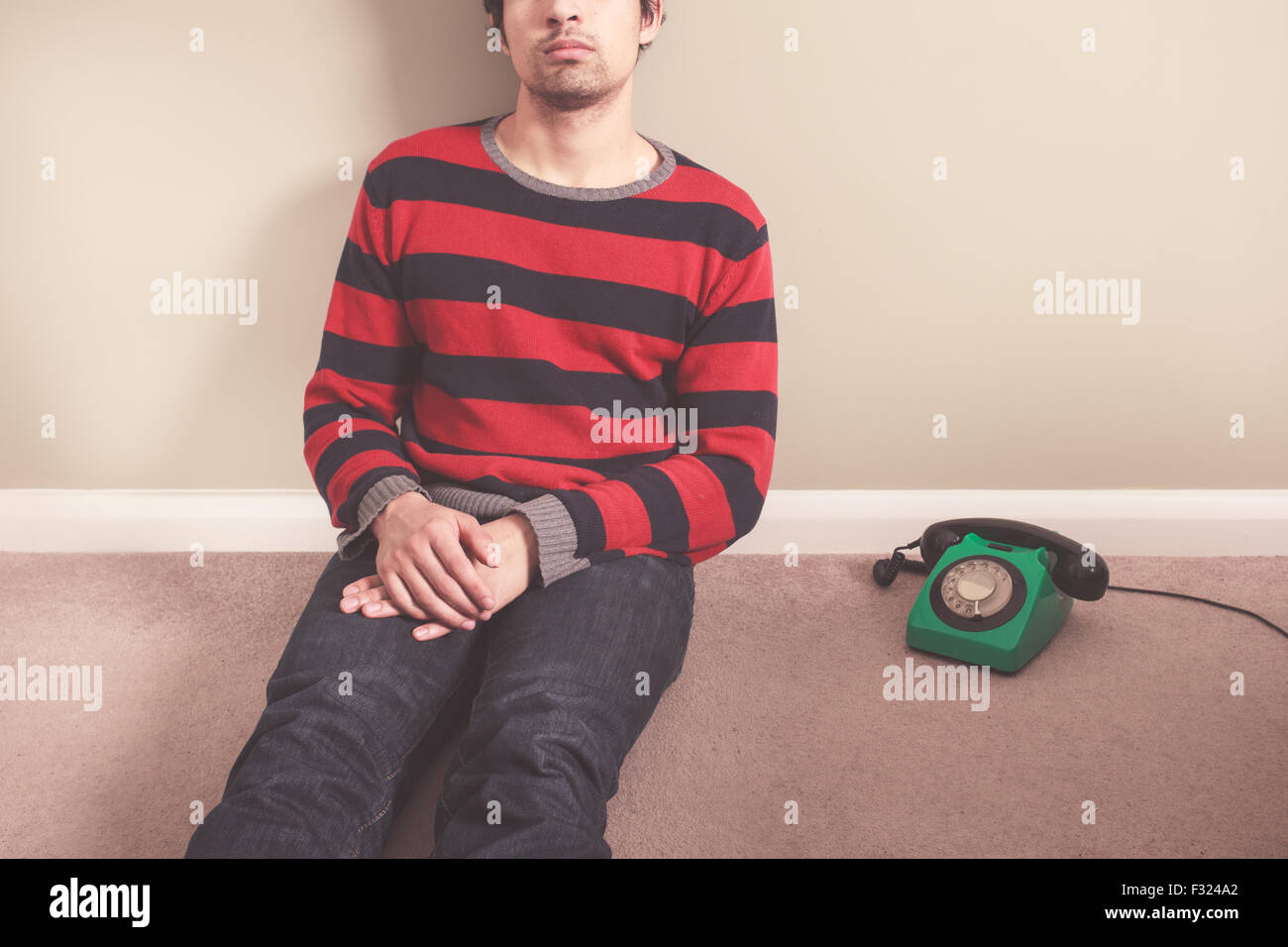 Young man is sitting on the floor with a telephone next to him - Stock Image