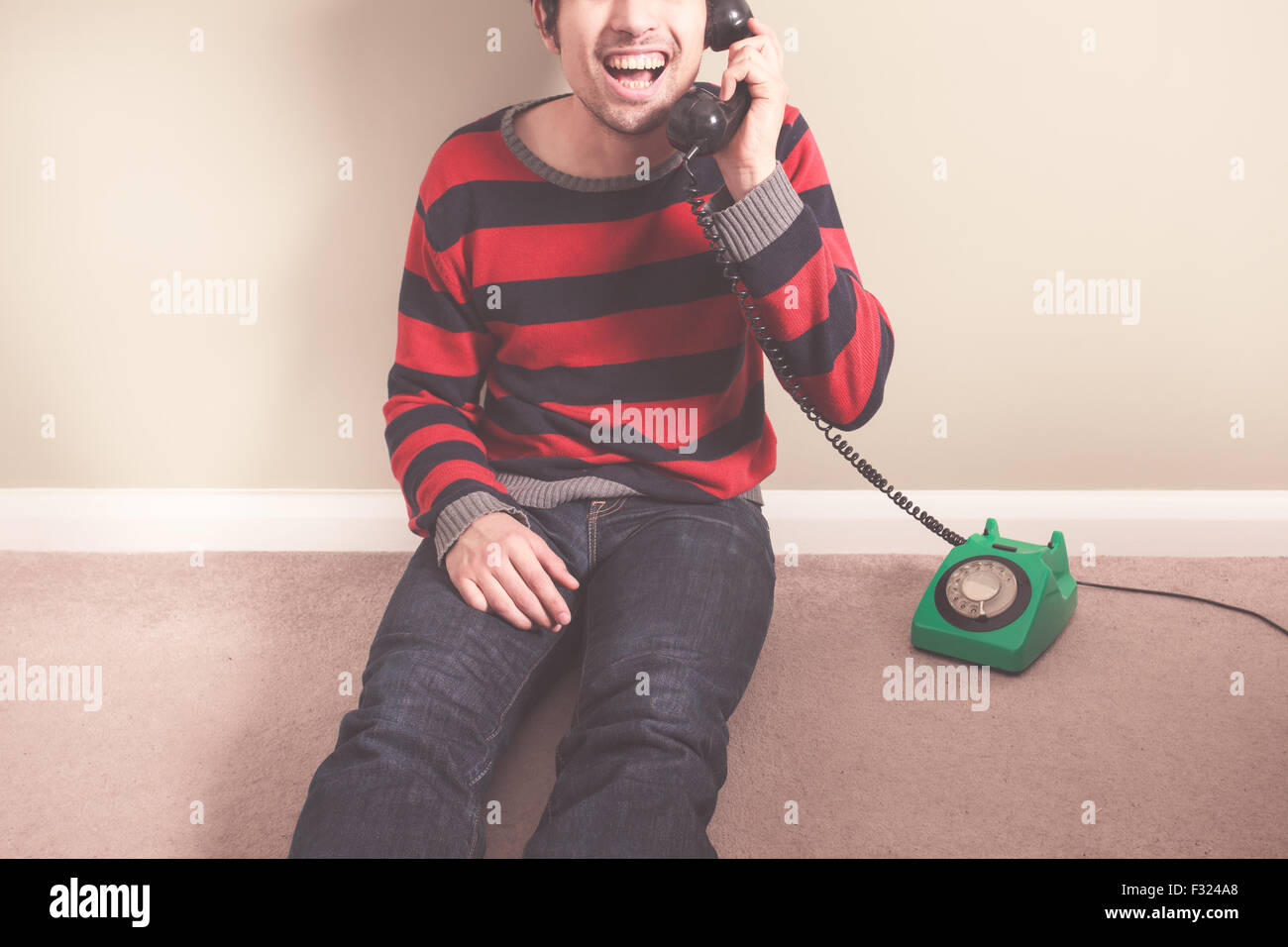 Happy young man is talking on the telephone - Stock Image