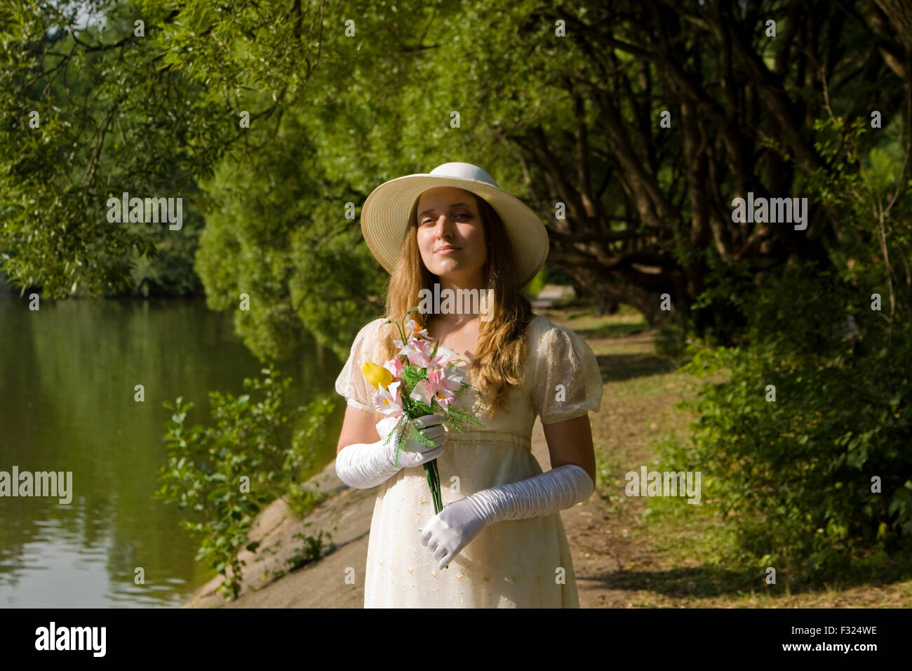Lady, half body, in white dress with white hat with bouquet of flowers in park. - Stock Image