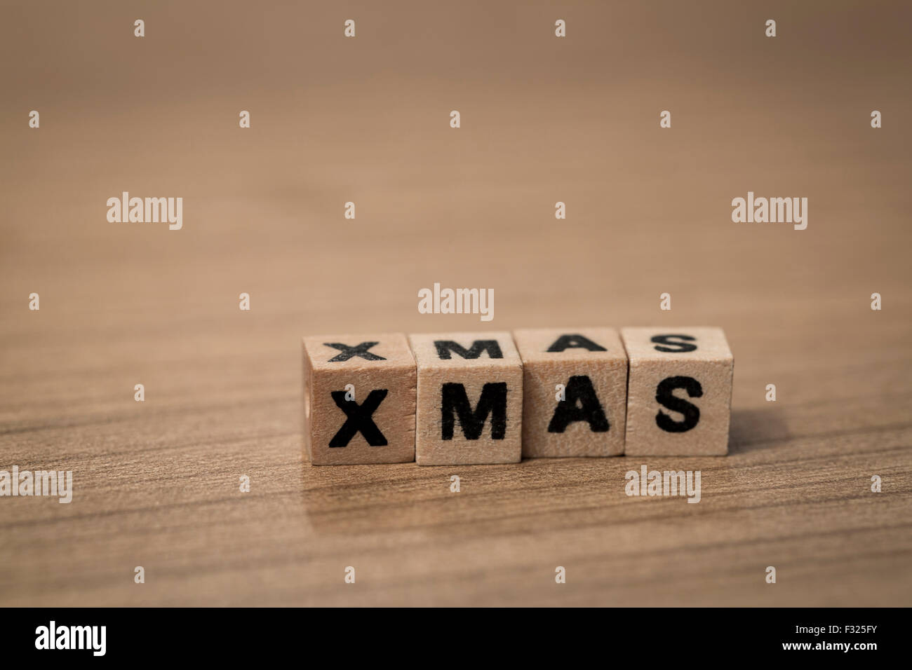 X-Mas written in wooden cubes on a desk - Stock Image