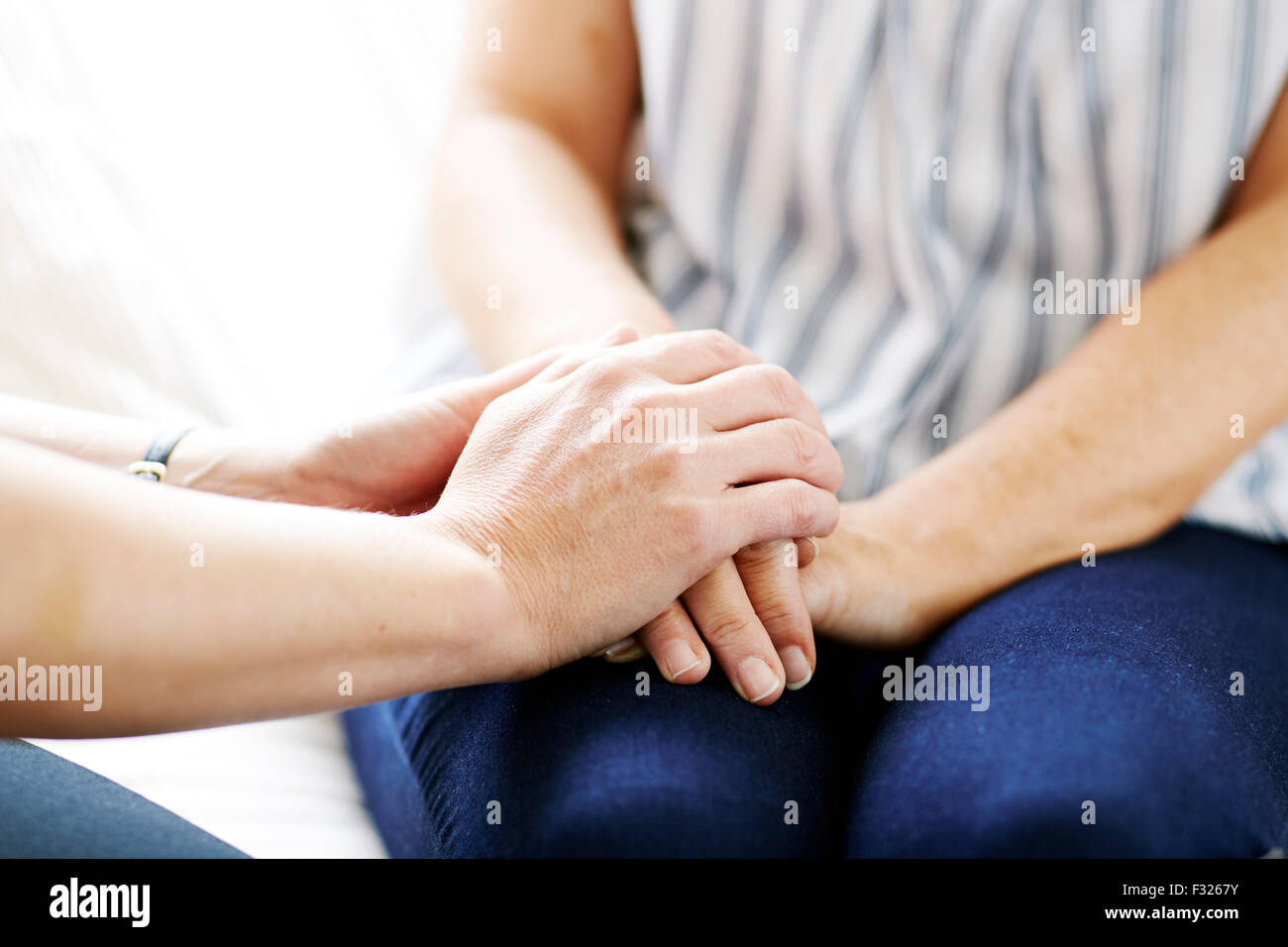Woman consoling another - Stock Image