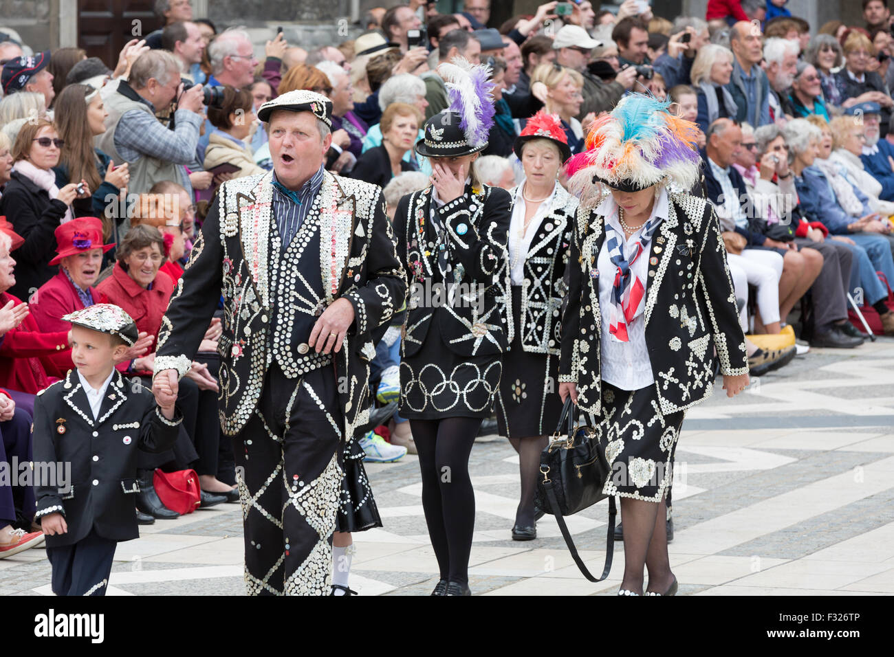 Pearly Kings and Queens celebrate the harvest festival, wearing their traditional pearl-button suits as they parade - Stock Image