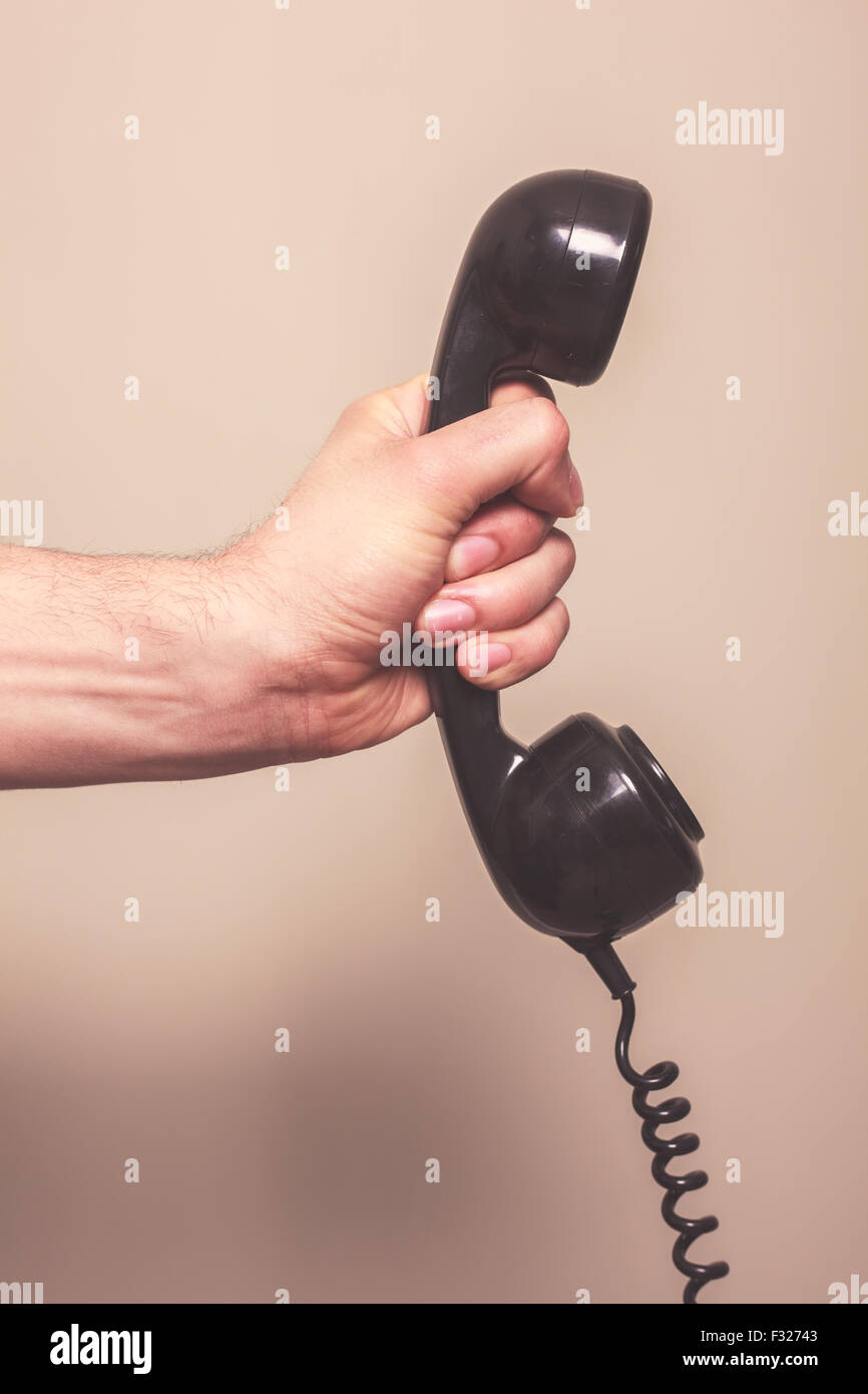 The hand of a man is holding a retro telephone receiver - Stock Image