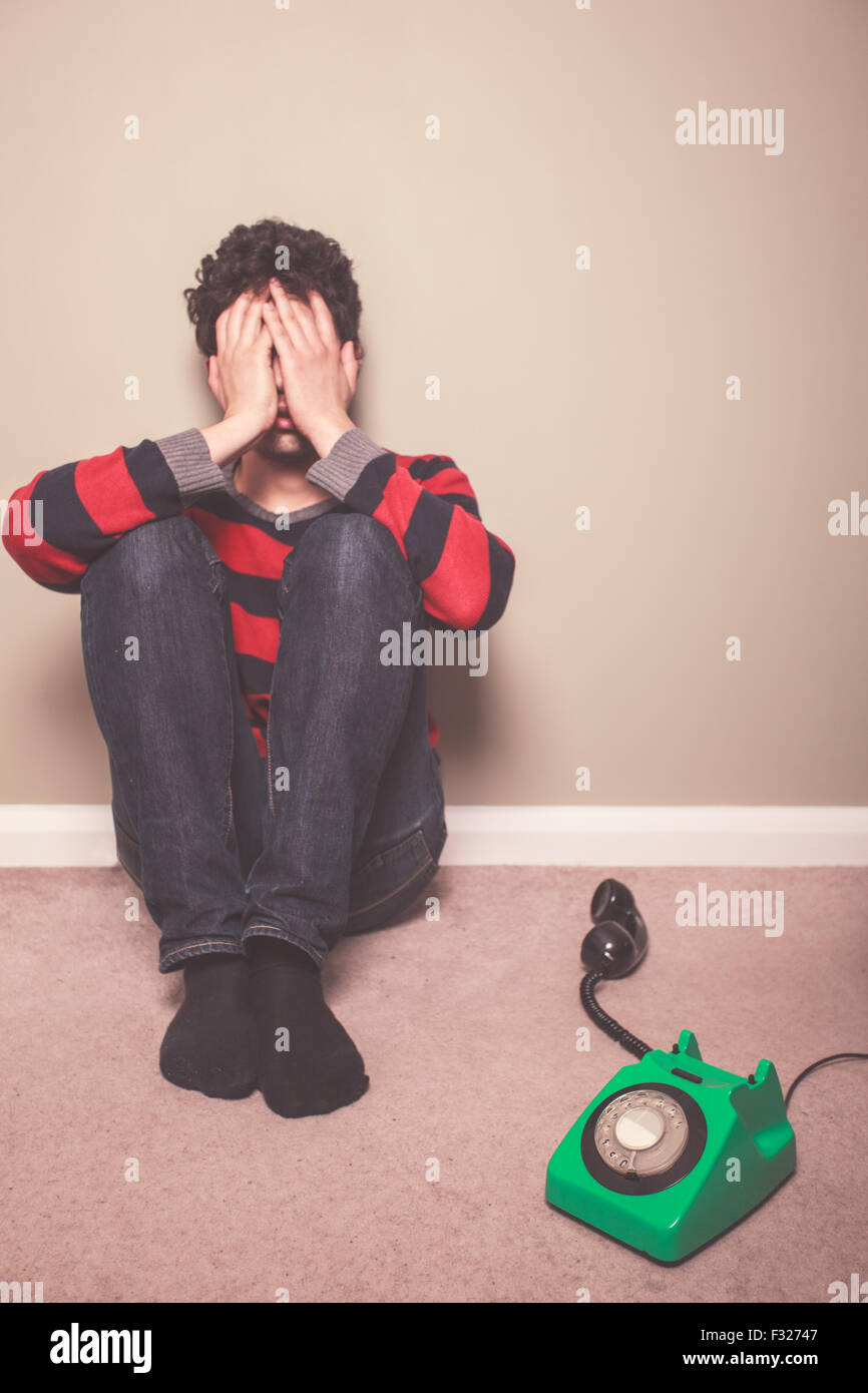 Tired and sad young man is sitting on the floor with a telephone - Stock Image