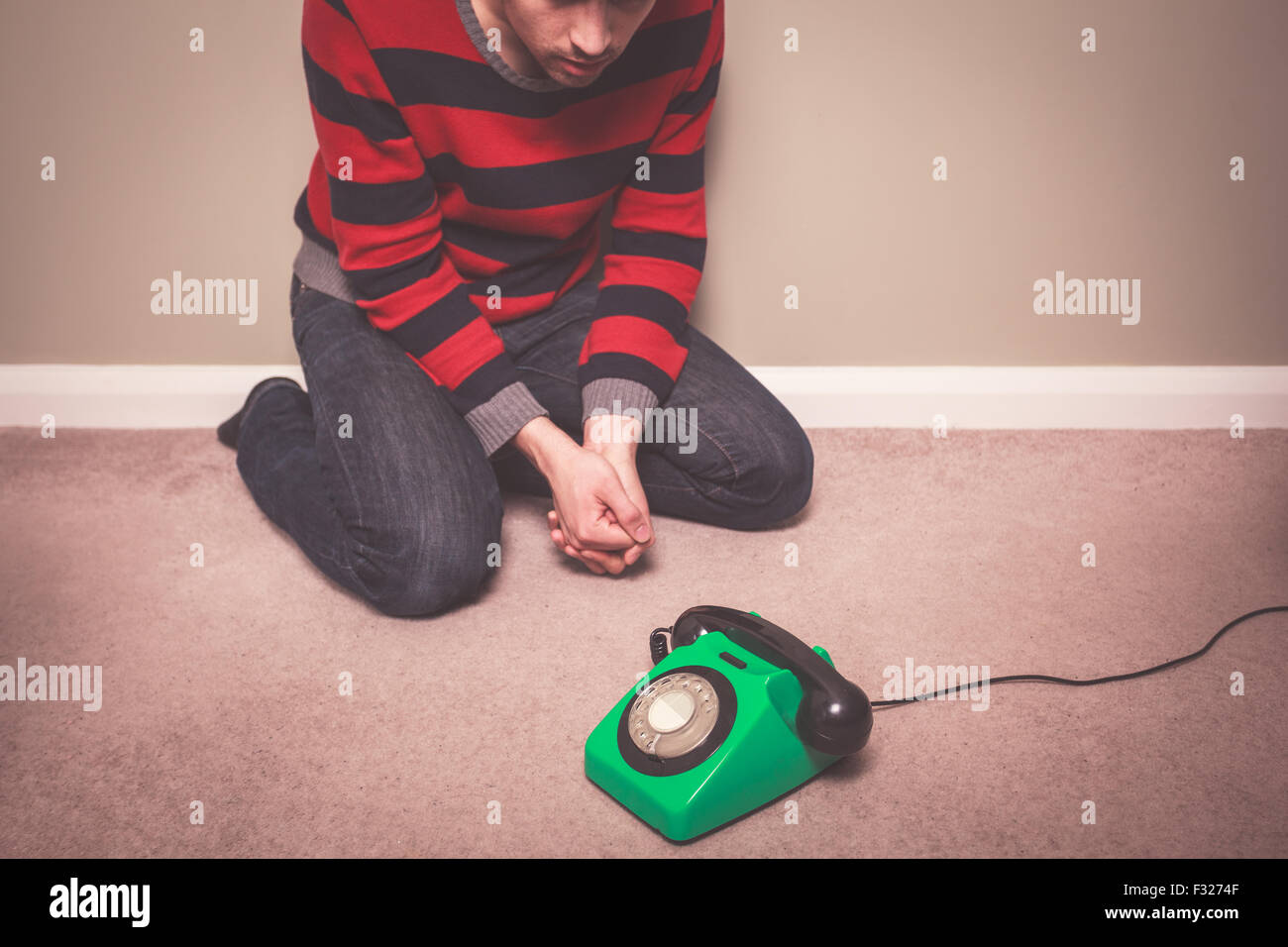 A young man is sitting on the floor and is desperately waiting for a phone call - Stock Image