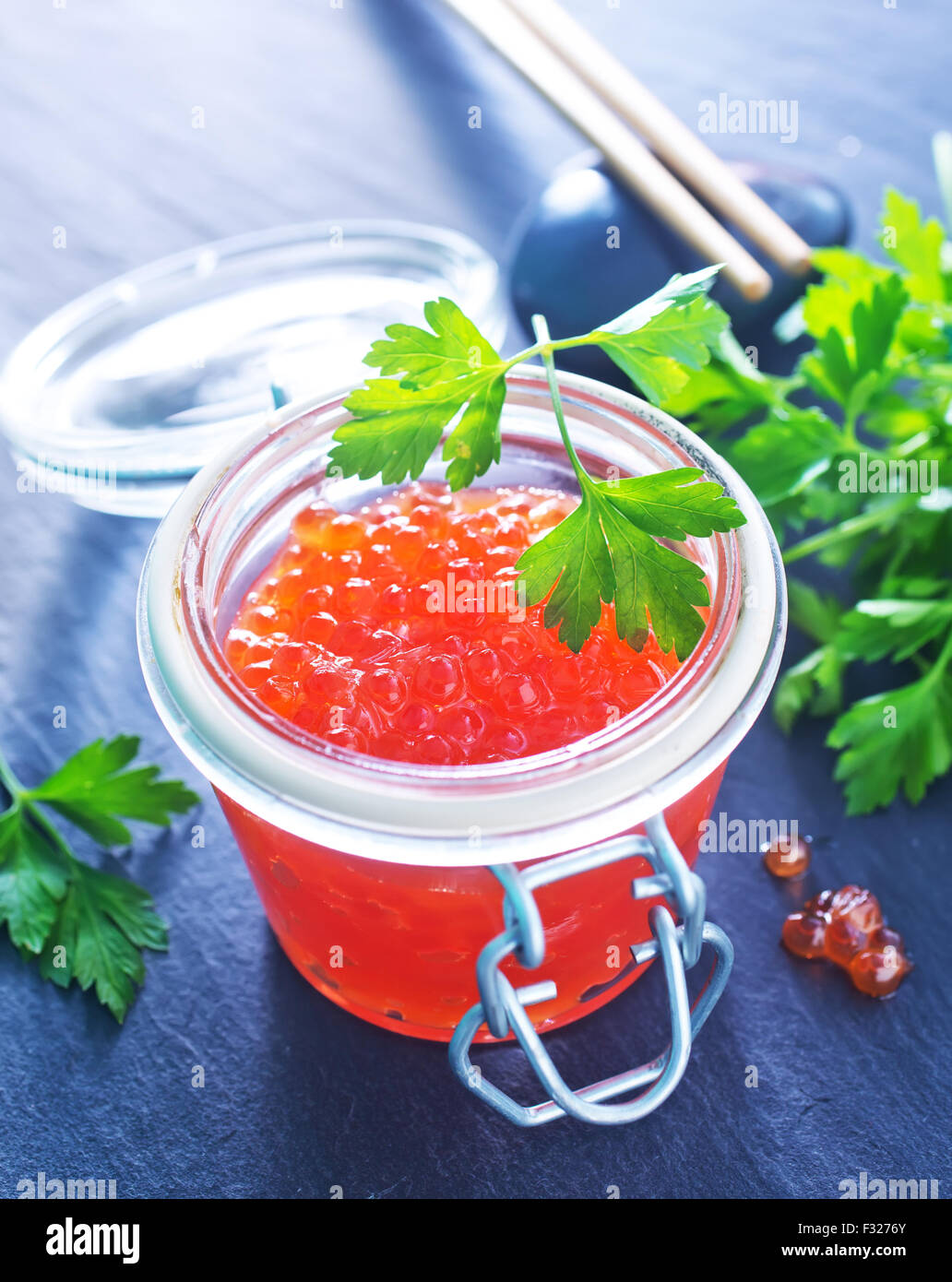 red salmon caviar in glass bank and on a table - Stock Image
