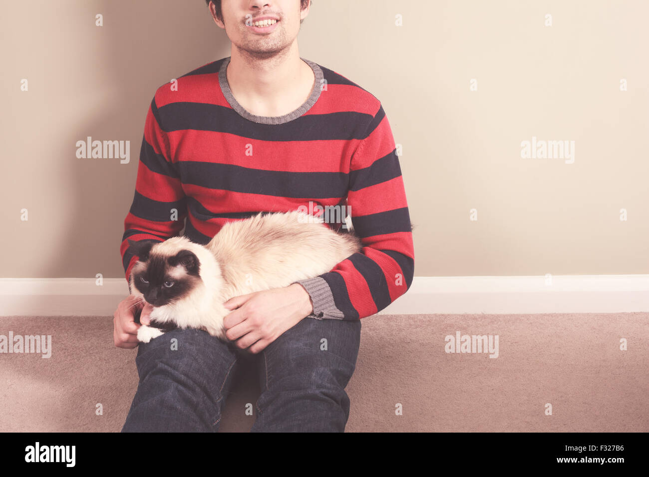 A young man is sitting on the floor and petting his cat - Stock Image