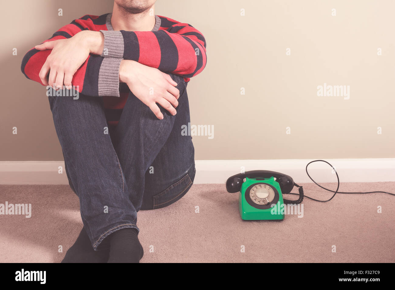 Young man is sitting on the floor with an old rotary telephone - Stock Image