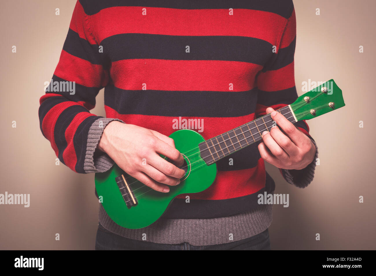 Young man in a striped jumper is playing ukulele - Stock Image