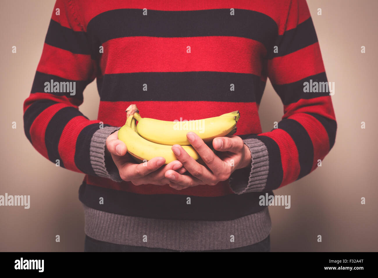 Closeup on a man in a striped jumper holding a bunch of bananas - Stock Image
