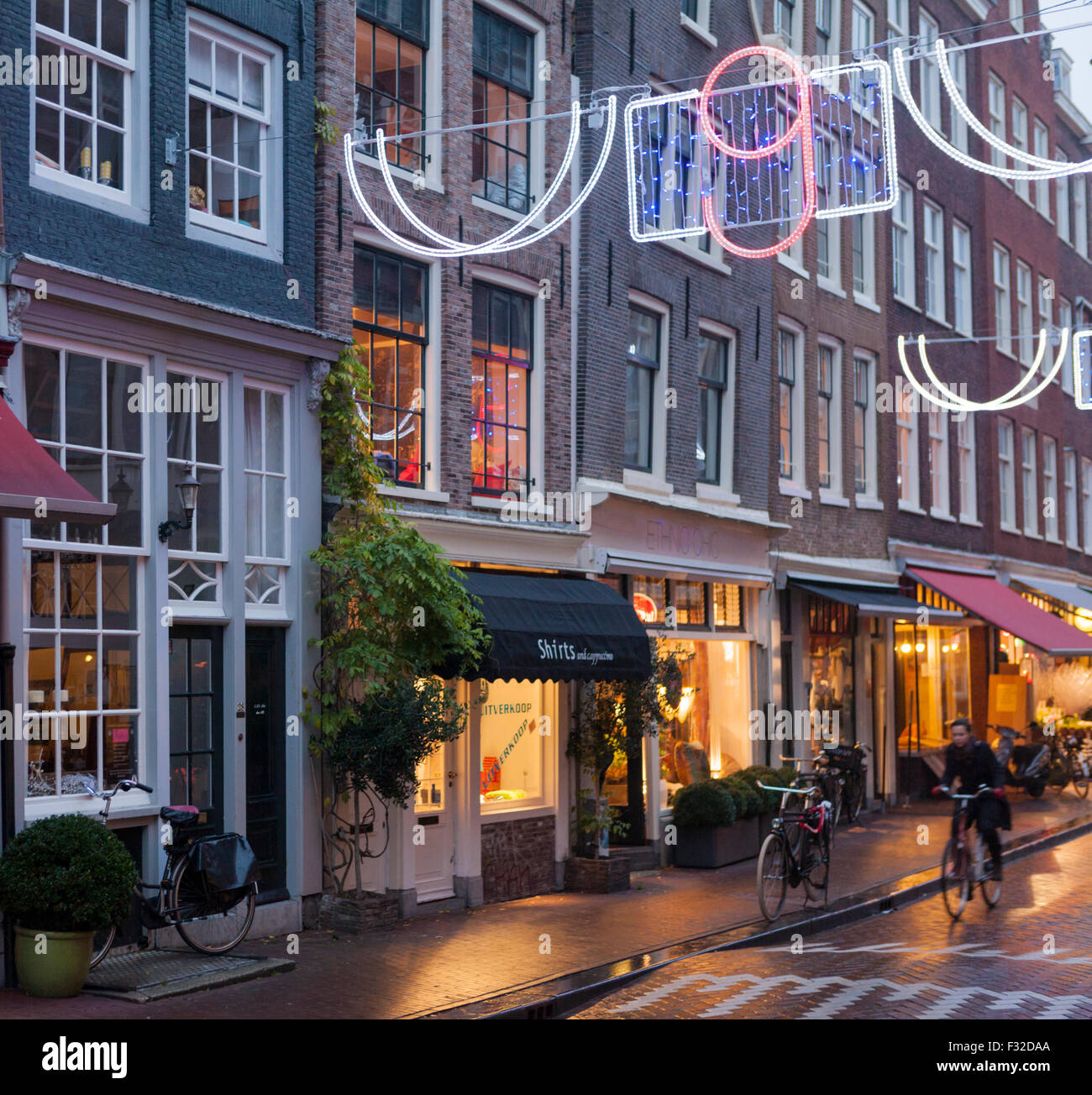 Bicyclist at dusk on Runstraat in the trendy Nine Streets shopping district, Amsterdam - Stock Image